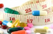 Medicine and Tape Measure on White Background in Waistline and Weight Control Concept. — Stockfoto