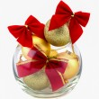 Christmas golden balls and red bow in a glass vase — Stock Photo #58054205