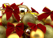 Christmas golden balls with red ribbons on a white background — Stock Photo