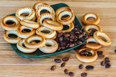 Ruddy bagels and coffee beans on a plate — Stock Photo