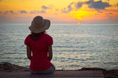 Young woman in hat sitting and looking at sunset — Stock Photo