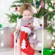 Cute smiling toddler girl checking her Christmas stocking under a decorated tree — Stock Photo #51828065