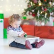 Toddler girl opening her Christmas present under a Christmas tree — Stock Photo #51828077