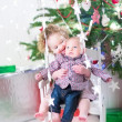 Adorable toddler girl holding her baby brother stting under Christmas tree — Stock Photo #51828479