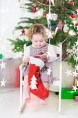 Cute smiling toddler girl checking her Christmas stocking under a decorated tree — Stock Photo
