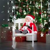 Cute newborn baby in santa costume in a dark room with beautiful Christmas tree — Stock Photo