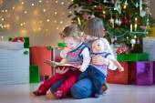 Portrait of three kids under a beautiful Christmas tree — Stock Photo