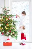 Adorable toddler girl helping her brother to decorate a Christmas tree — Foto de Stock