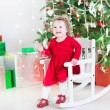 Funny curly toddler girl playing with a red bell in a rocking chair under a Christmas tree — Stock Photo #52399683