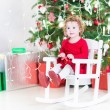 Cute curly toddler girl in a red dress relaxing in a rocking chair under a Christmas tree — Stock Photo #52399707
