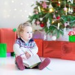Beautiful little toddler girl reading a book sitting under a decorated new year tree — Stock Photo #52399733
