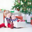 Little toddler girl and her newborn brother helping to decorate new year tree — Stock Photo #52399777