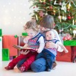 Portrait of thre kids sitting under a beautiful Christmas tree — Stock Photo #52399781