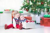 Little toddler girl and her newborn brother helping to decorate new year tree — Стоковое фото