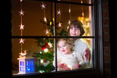 Kids at window on Christmas eve — Stock Photo