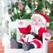 Adorable newborn baby boy in Sante outfit sitting under Christmas tree — Stock Photo #53482149