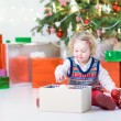 Portrait of a little toddler girl in a warm sweater under Christmas tree with present — Stock Photo #53482225