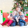 Three happy children sitting under a beautiful Christmas tree — Stock Photo #53482263