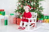 Cute toddler girl in a red dress and santa hat sitting under Christmas tree — Stock Photo