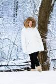 Beautiful young woman in a warm white jacket walking in a snowy park — Stock Photo