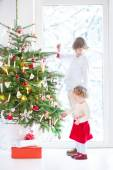 Beautiful toddler girl helping her brother to decorate a Christmas tree — Стоковое фото
