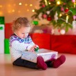Little girl opening her Christmas present — Stock Photo #53549231