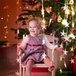 Little girl in rocking chair under Christmas tree — Stock Photo #53549335