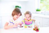 Kids eating fruit and cereal — Stock Photo