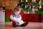 Little girl reading at Christmas tree — Stock Photo