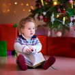 Little girl reading at Christmas tree — Stock Photo #53996147