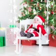 Cute newborn baby boy in Santa costume sitting under a Christmas tree — Stock Photo #54708421