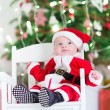 Little newborn baby boy in Santa outfit sitting under a Christmas tree — Stock Photo #54708425