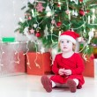 Cute little toddler girl in a santa hat and red dress playing under decorated Christmas tree — Stock Photo #54708431