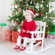 Cute toddler girl in a red dress and santa hat sitting under decorated Christmas tree — Stock Photo #54708443