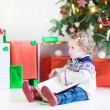 Adorable toddler girl reading a book sitting under  Christmas tree — Stock Photo #54708459
