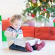 Portrait of a cute curly toddler girl opening Christmas present — Stock Photo #54708469