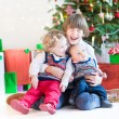 Three happy children under Christmas tree — Stock Photo #54708499