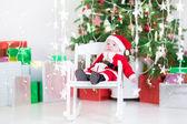 Cute newborn baby boy in Santa costume sitting under a Christmas tree — Stok fotoğraf