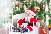 Little newborn baby boy in Santa outfit sitting under a Christmas tree — Stock Photo
