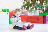 Portrait of a cute curly toddler girl opening Christmas present — Stock Photo