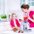Mother and daughter making fresh fruit jiuce — Stock Photo #54835063