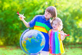 Kids playing with airplanes and globe — Stock Photo