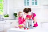 Mother and daughter making fruit juice — Zdjęcie stockowe