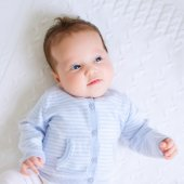 Newborn in white and blue on a white blanket — Stock Photo