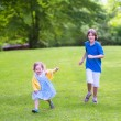 Happy kids running in a park — Stock fotografie #55896111
