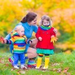 Mother and children in an autumn park — Stock Photo #56943017