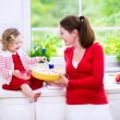 Mother and daughter baking a pie — Stock Photo #58724553