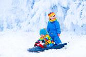 Little children enjoying a sleigh ride — Stock Photo