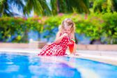 Little girl drinking juice at a swimming pool — Stock Photo
