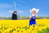 Dutch girl in tulip field in Holland — Stock Photo